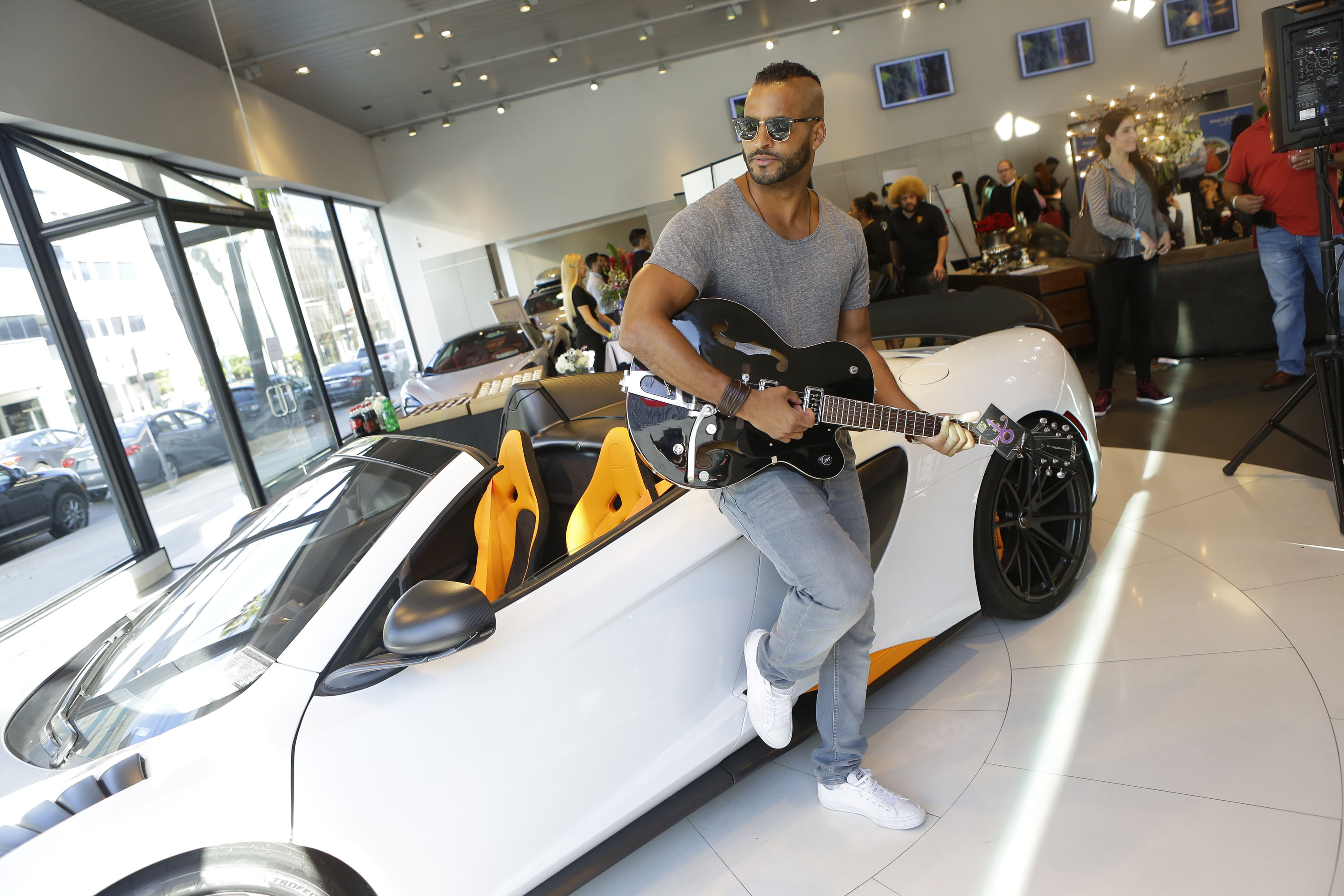 Actor Ricky Whittle holding the signed Price guitar (Photo by Tiffany Rose/Getty Images for GBK)