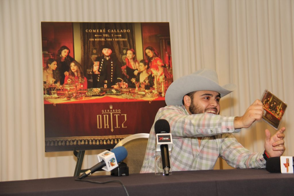 Gerardo Ortiz holding up album copy during press conference (Photo by: Fredwill Hernandez/The Hollywood 360)